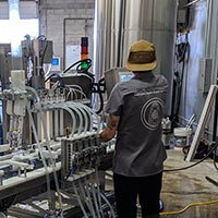 Danielle with her back turned toward the canning line at Device Brewing