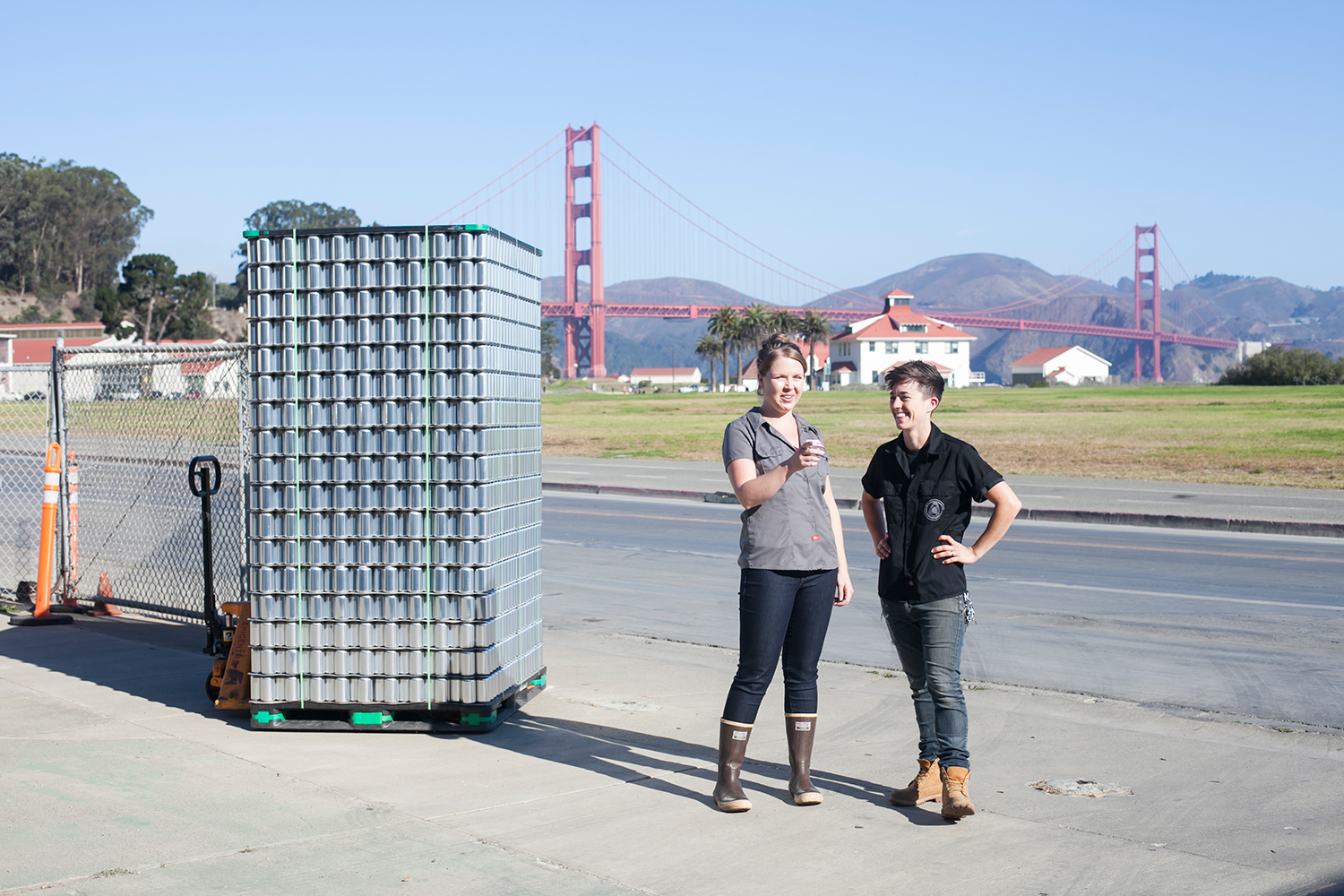 Owners, Jenn and Lindsey, standing in front of the Golden Gate Bridge next to a pallet of empty aluminum cans