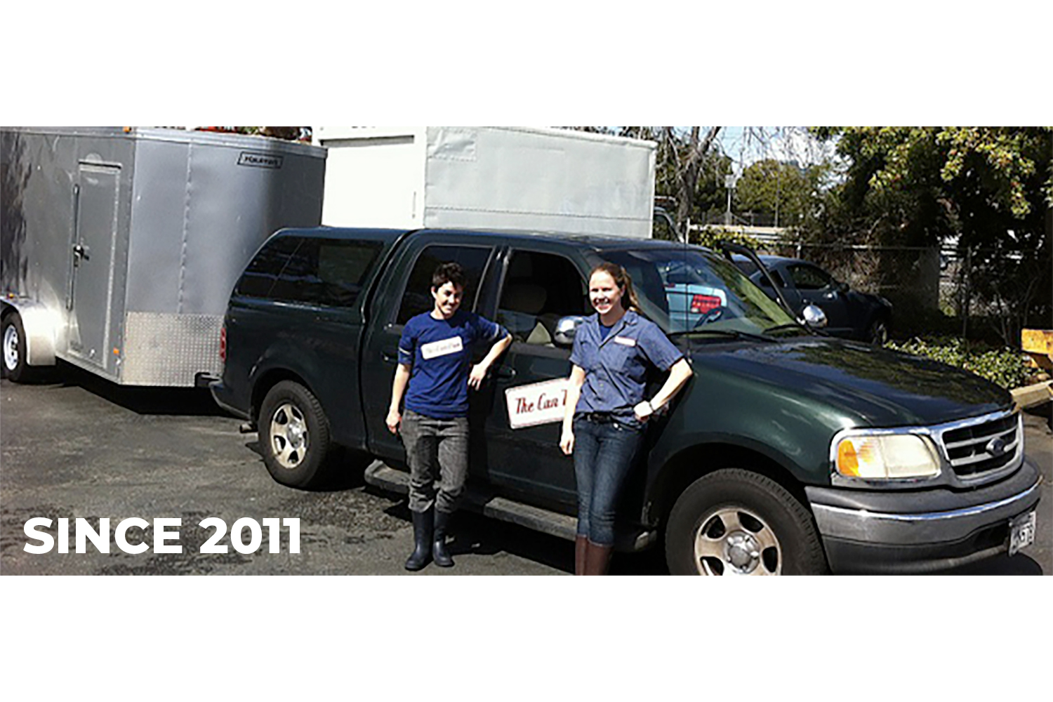 Owners, Jenn and Lindsey, standing in front of their first truck and trailer in 2011