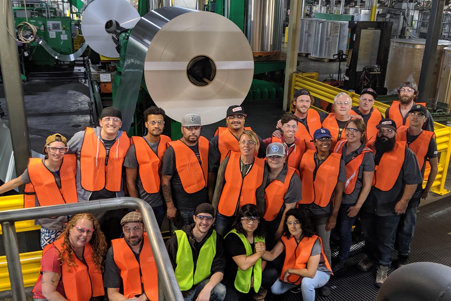 Team posing for photo at the Ball Corporation with machinery in the background
