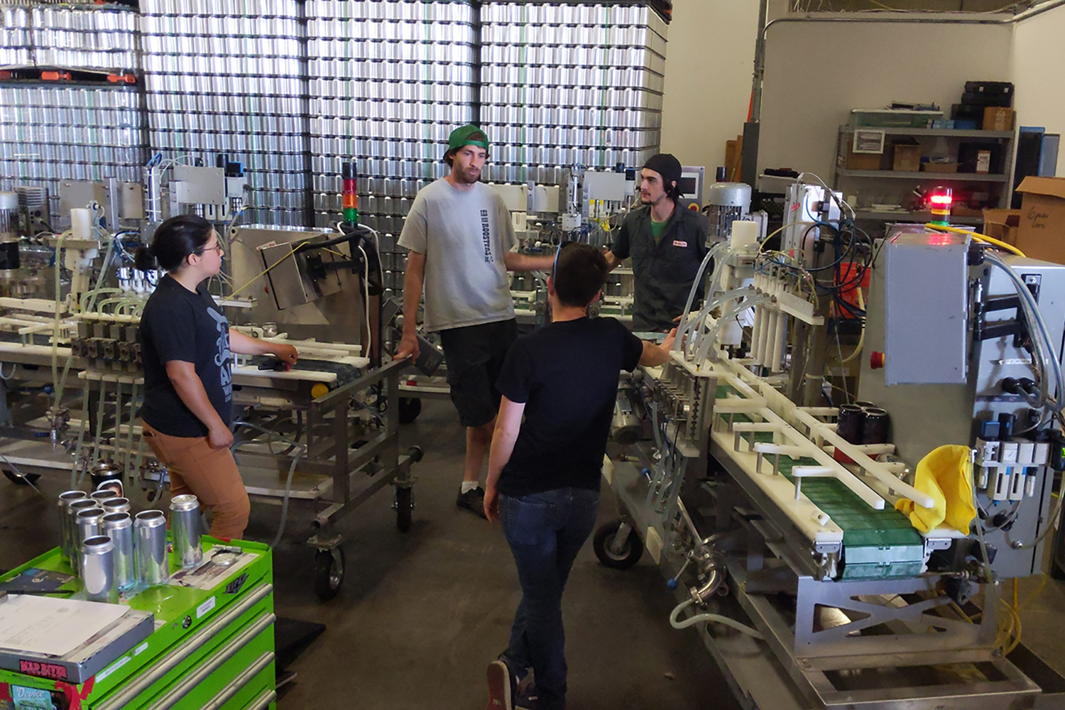 Sarah, Wade, Lindsey, and Camreon having a chat in the warehouse next to a couple of the canning lines